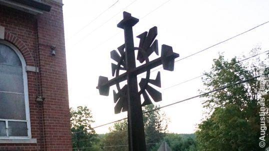 The metal Lithuanian sun-cross in front of the Athol church