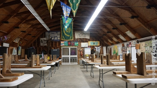 Interior of the main hall of Romuva, filled with flags, posters, bas-reliefs and other artworks created in the decades by the participants of the summer camps