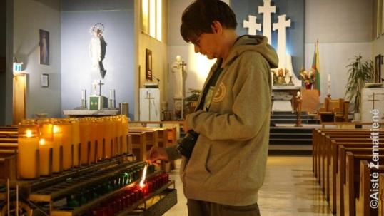 Augustinas uždega žvakutę Aušros Vartų bažnyčioje