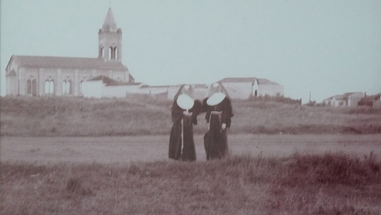 This image that hangs on the school wall shows Vila Zelina district during its construction in the 1930s; the Lithuanian church is already built while the rest is still mostly a field. Lithuanian Franciscan nuns stand in front