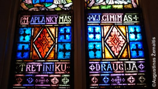 A close-up of Waterbury Lithuanian church stained glass window with Lithuanian inscriptions