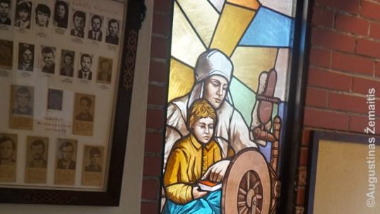 """Lenta su 1991 01 13 aukų portretais (kairėje) ir vitražas, kuriame vaizduojama """"vargo mokykla"""" – slaptos pamokos lietuvių kalbos draudimo laikotarpiu, Lietuvą valdant carinei Rusijai (1965–1904 m.)"""