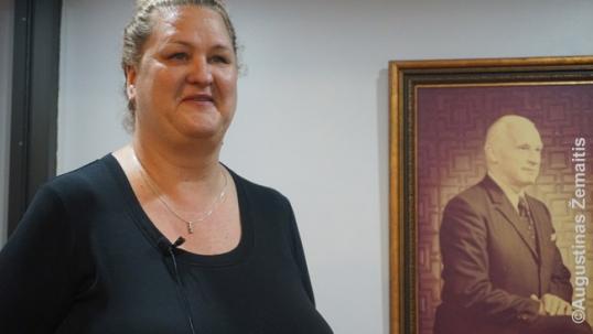 """Kredito unijos """"Talka"""" darbuotoja duoda interviu priešais įkūrėjo portretą"""